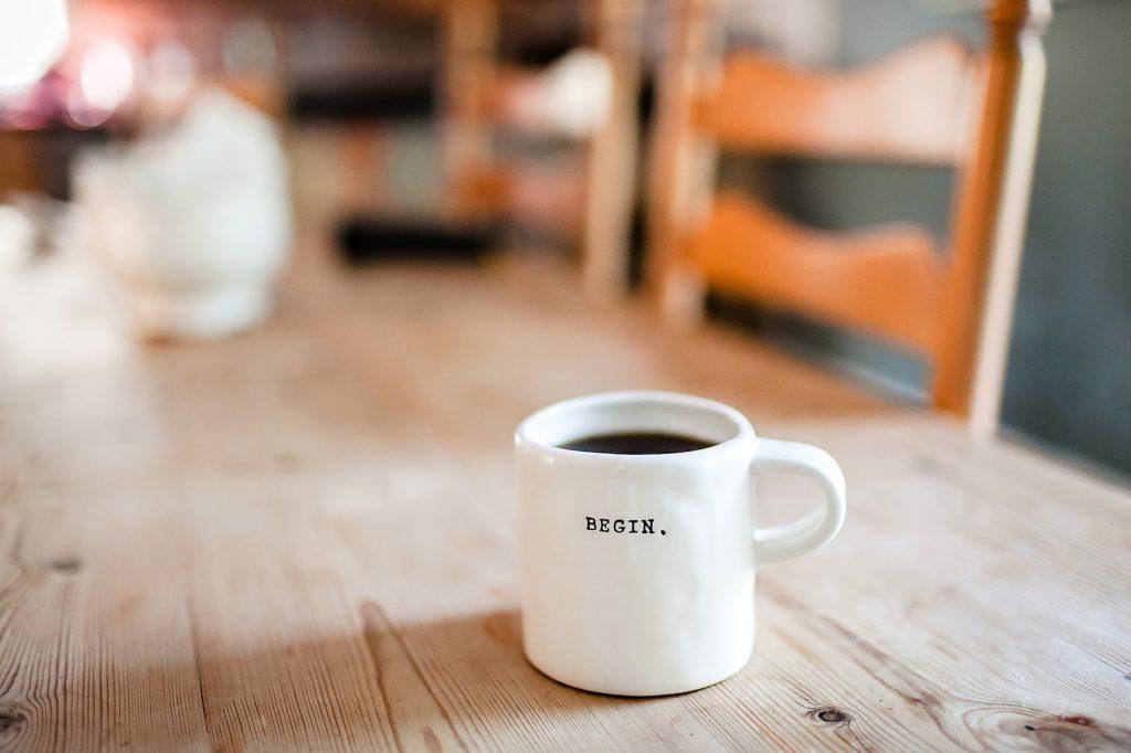 """Tasse mit Aufschrift """"Begin"""" auf einem Holztisch"""