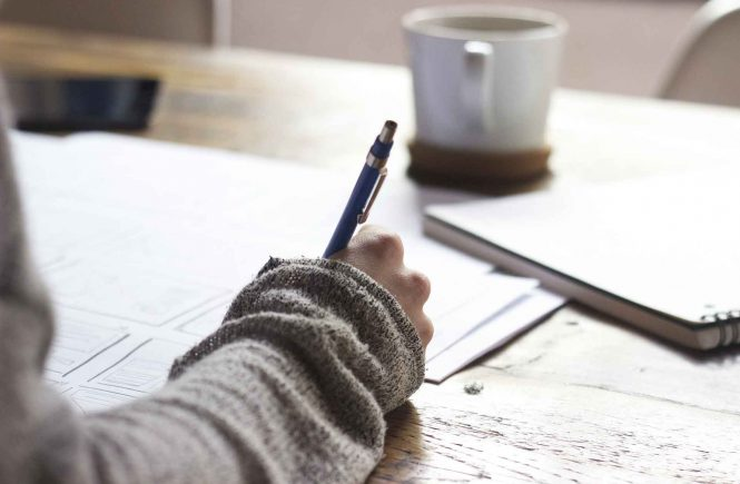 Frau sitzt am Tisch und schreibt