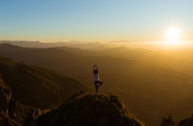 Frau macht Yoga auf einem Berg bei Sonnenuntergang