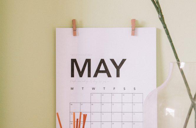 Weißes Kalenderblatt des Monats Mai an einer gelben Wand, davor eine Vase mit Blumen