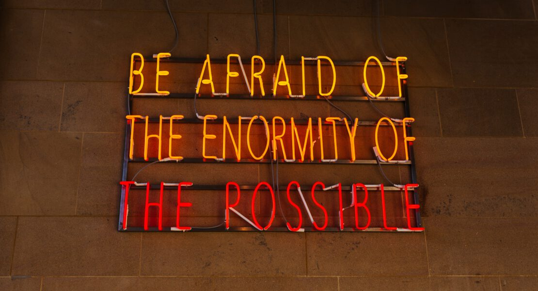 "Glowing sign saying ""Be afraid of the enormity of the possible"""